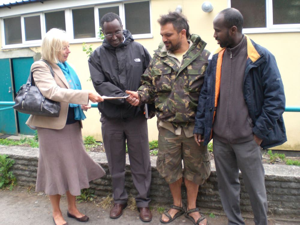 Representatives from the Somali Resource Centre receiving a cheque as a contribution for fruit trees in the Peace Garden in front of the community mosque in Barton Hill