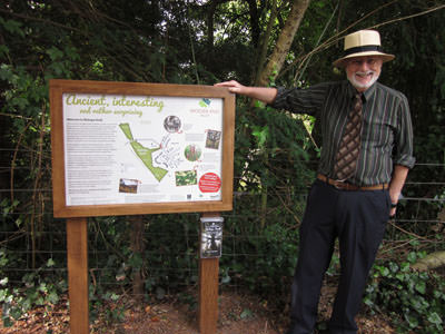 Bev Knott, Chairman of Friends of Bishop's Knoll Wood, with a new information board featuring AGT logo